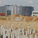 Construction Machinery Working At The Construction Site: a Grader Loads The Sand Into a Dump Truck