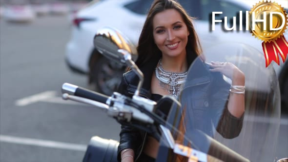 Download Woman Biker Smiles and Straightens Hair Sitting nulled download
