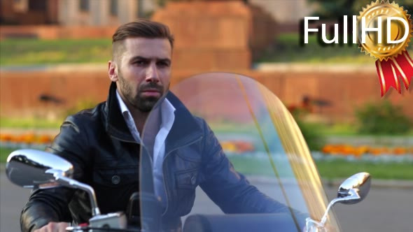 Download Biker in a Leather Jacket Sits on His Motorcycle nulled download