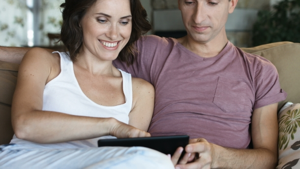 Download Attractive Young Couple Relaxing Together At Home With a Computer Tablet. nulled download