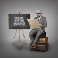Dream. Explore. Discover. text on blackboard with explorer businessman