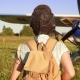Girl Going To An Old Airplane