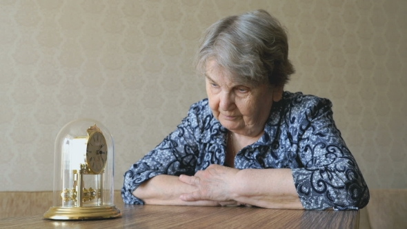 Download Old Woman Looks At The Table Clock With Pendulum nulled download