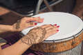 Women's hands decorated with traditional Indian painting on the drum