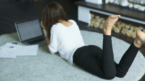 Download Young Brunette Lying On The Carpet And Using Laptop nulled download
