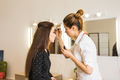 Make-up artist doing makeup for young woman