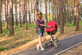 family, child and parenthood concept - happy mother walking with baby stroller in park