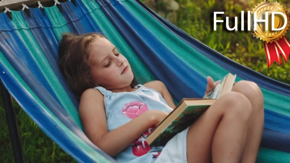 Download Young Curly Girl Reads a Book Lying in a Hammock nulled download