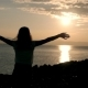 Silhouette Of Wonderful Young Woman Watching To Sea And Raising Her Hands