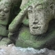 Two Stone Statues in the Moss on the Beach, Lapped by the Waves