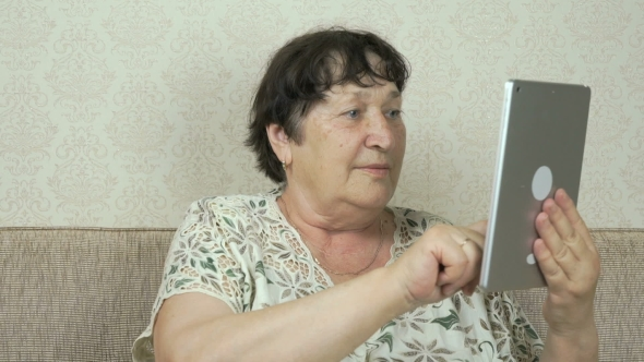 Download Elderly Woman Holding a Silver Digital Tablet nulled download