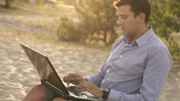 Download Recreational Entrepreneur. Man With Laptop In The Morning On The Beach Working nulled download