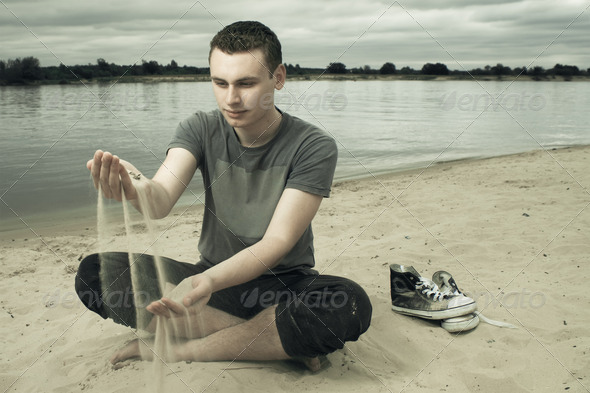 Thoughtful Yaoung Man Sitting On The Beach During Stormy Weather - Stock Photo - Images