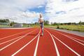 Fast athletic female runner on outdoor running track