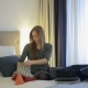 Female Carefully Packing a Suitcase In Hotel
