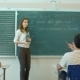 Young Female Teacher Writing On Chalkboard In Class