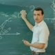 Male Teache Washes The Chalkboard In Classroom