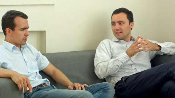 Download Two Young Male Friend Sitting On Sofa And Chatting At Room. Men Talk Concept. nulled download