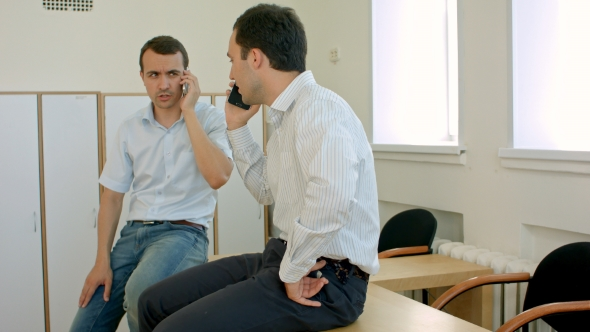 Download Two Smiling Students With Mobile Phone In Hands Are Having Pleasant Conversation In Room nulled download