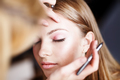 pretty girl applying make up by makeup artist