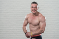 Muscular Man Flexing Muscles On White Bricks Background