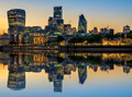 Illuminated London Cityscape at Sunset with Reflection