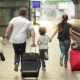 Young Family Of Two Spouses, Son And Daughter, Running To Catch The Train Before It Leaves The