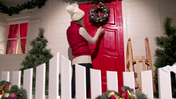 Download Young Woman Is Decorating The Front Door Of The House With a Fur Wreath On a Christmas Eve Night nulled download