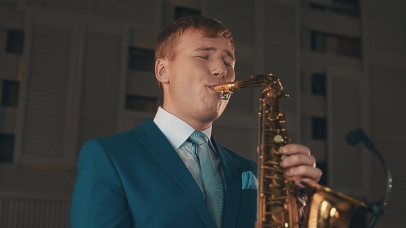 Download Saxophonist In Blue Suit Play Jazz On Golden Saxophone With Microphone. Music. nulled download