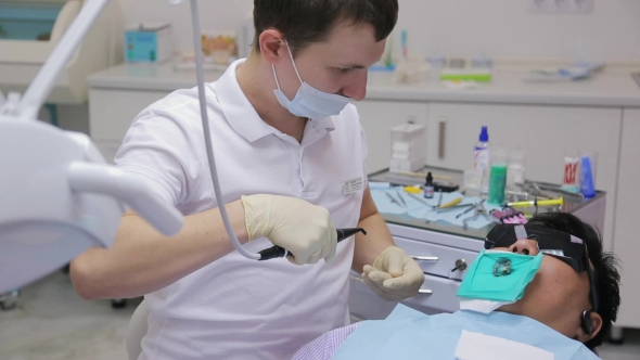 Download Young Stomatologist Sits Near Patient In Working Cabinet nulled download