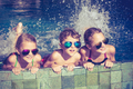 happy children  playing on the swimming pool at the day time