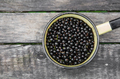 Black currants top view in bowl on rustic wood background