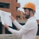 Chief Architect At Construction Site. Chief Architect In a Hard Hat At Construction Site Looking At