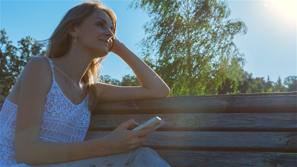 Download Happy Smiling Girl Using SmartPhone in City Park Sitting on the Bench  nulled download