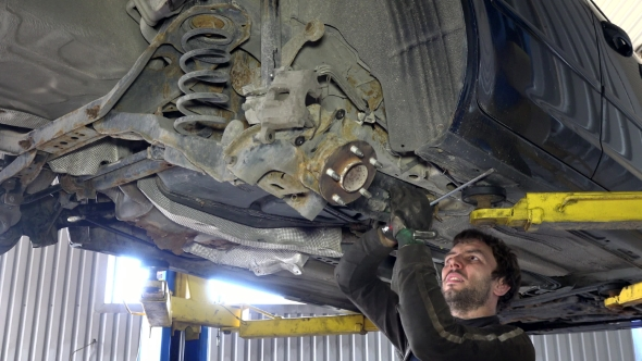 Download Skilled Mechanic Removing Worn Car Parts in Garage Under Automobile. nulled download