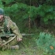 The Young Man In Uniform With a Weapon In His Hands. He Is Sitting In The Forest, Resting, Looking