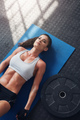 Fit young woman relaxing after heavy weight workout