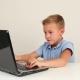 Cute Teen Boy Working On Laptop Computer Or Watching Video In Internet