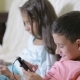 Boy And Girl Sitting On The Couch With Your Phone. Online Games
