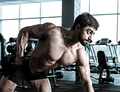 bodybuilder training back with dumbbell in the gym