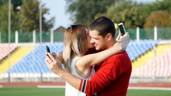 Download Young Guy And Beautiful Girl Reading a Message On Your Mobile Phone - On The Football Field nulled download