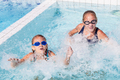 Two happy children  playing on the swimming pool at the day time