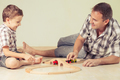 Daddy with little boy playing with toy train on the floor at the