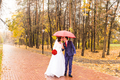 Just married couple under umbrella walking on road at park