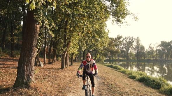 Download Man Rides a Bike Near Lake nulled download