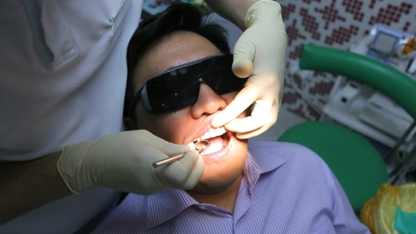 Download Dentist Is Healing Client Teeth With Mouth Mirror. nulled download