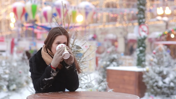 Download Beautiful Young Woman Drinking Hot Tea During Christmas Fair nulled download