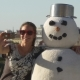 Girl Photographs Selfie In An Embrace With a Snowman In Belvedere