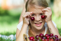 Happy little girl lying near the tree with a basket of cherries