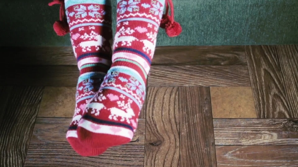Christmas Female Legs In Socks On The Background